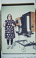 Elsa Dorfman's portrait next to her 20x24 Polaroid camera